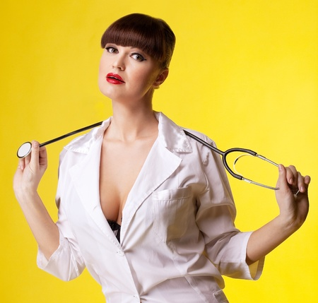 Attractive woman in nurse costume with stethoscope look at you photo