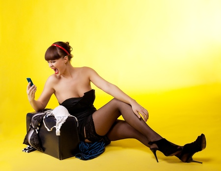 Beauty anger woman sit on broken baggage and scream on cell - pin-up style Stock Photo - 9256952