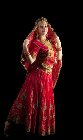 young girl dance in gorgeous red indian oriental costume photo