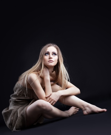 Beauty blond girl in rag from dark look at light Stock Photo - 9313181