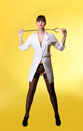 Attractive woman in sexy nurse suit and lingerie with stethoscope on yellow - ppinup style photo
