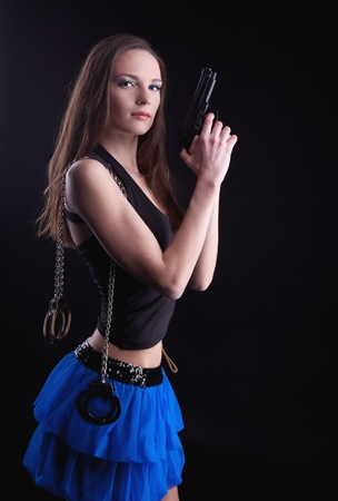 young beauty girl with long hair, gun and handcuffs Stock Photo - 9391703