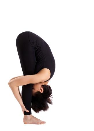 young woman training in yoga asana - uttanasana stand pose isolated photo