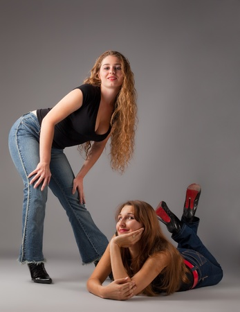 Two beauty woman look at you - contemporary jeans style photo