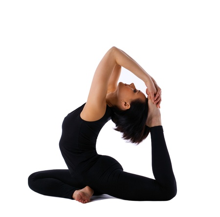 young woman training in yoga asana - pigeon pose isolated photo