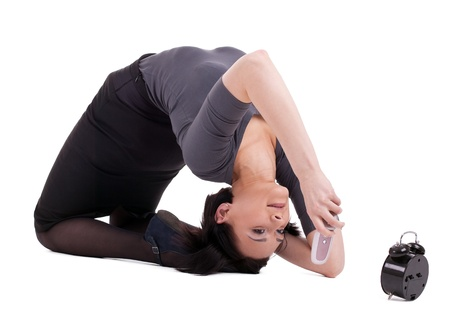 Young businesswoman lay in yoga pose talk on cell befor clock photo