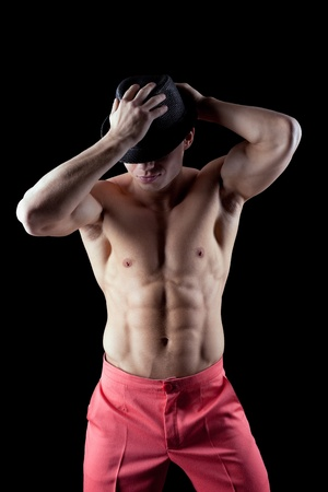 athletic man show striptease in dark with hat