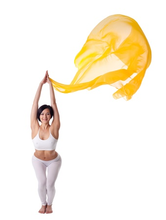 Young beauty woman in yoga uttkatasana and yellow flying fabric isolated Stock Photo - 9653091
