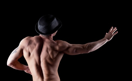 nude male: Young nude athletic man show striptease with hat in dark