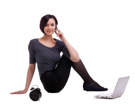 Young business woman sit with laptop and clock - talk on cell phone isolated photo