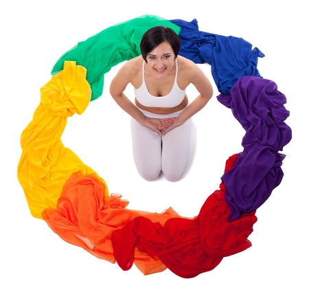 chakra energy: Young smile woman in yoga pose in ring of color fabric - rainbow isolated