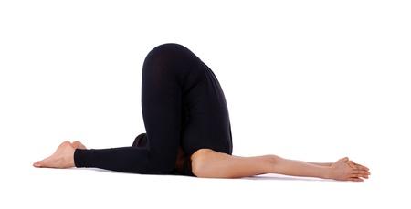 young woman doing yoga asana inversions - halasana isolated photo