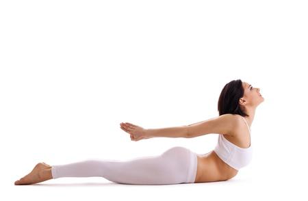 bhujangasana: young woman training in yoga asana - cobra bhujangasana pose