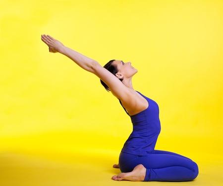 young woman training in yoga asana - pigeon pose on yellow photo