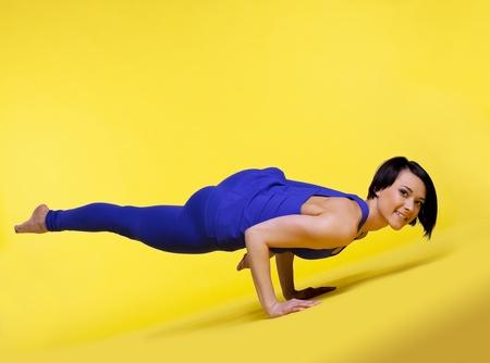 young woman training in yoga - Eka Pada Koundiyanasana arm balance pose photo