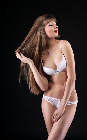 Young beauty girl posing in white lingerie in dark Stock Photo - 9700268