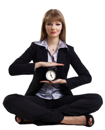 Yong business woman sit in yoga pose with clock - isolated photo