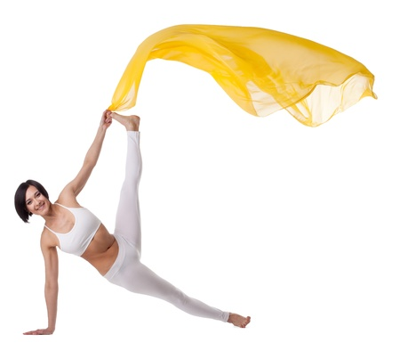 Young beauty woman in yoga asana and yellow flying fabric isolated Stock Photo - 9793646