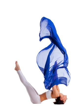 Young beauty woman in yoga asana and blue  cloth in air isolated Stock Photo - 9793648