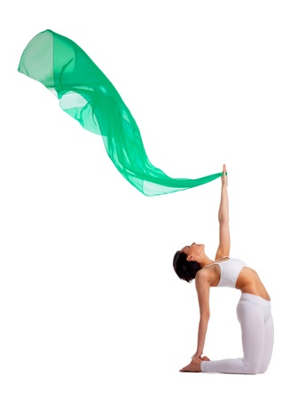 woman in yoga camel pose with green flying veil in air isolated