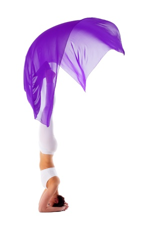 Young beauty woman in yoga asana stand on head with purple fabric isolated Stock Photo - 9793645