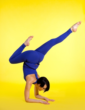 woman stand on hands in yoga pose - blue on yellow photo