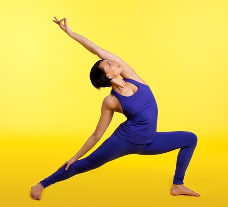 Young woman exercise and smile in yoga pose - blue on yellow photo