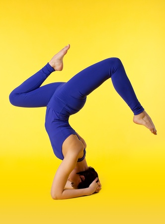 woman stand on hands in yoga pose - blue on yellow