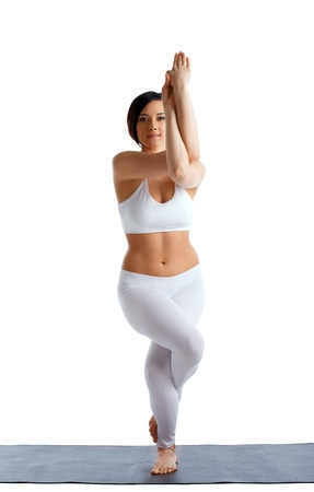 young beauty woman doing yoga asana in white on rubber mat isolated Stock Photo