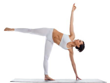 young woman training in yoga asana on rubber mat half moon pose isolated photo