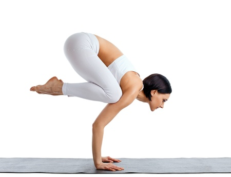 Young woman in white doing yoga pose arm balance on rubber mat isolated