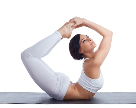 pilates studio: Beauty girl in back bends yoga - bow pose on rubber mat isolated