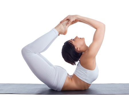 Beauty girl in back bends yoga - bow pose on rubber mat isolated Stock Photo - 10104215