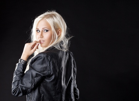 Pretty young blond girl look at camera with desire in leather photo