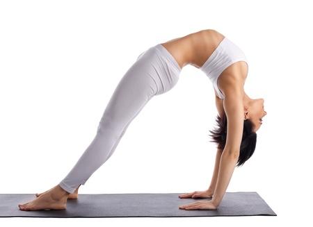 yoga mat: young woman doing yoga bridge pose on rubber mat isolated