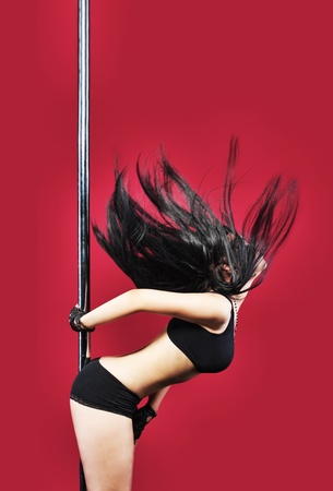 Woman in lingerie pole dance with black hair on red Stock Photo - 10300637