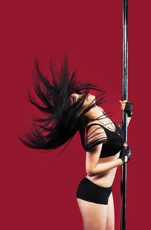 Young girl in lingerie in pole dance with black hair on red Stock Photo - 10300636