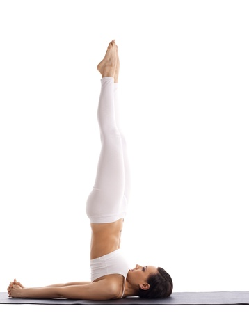 young woman in white stand on neck yoga isolated photo