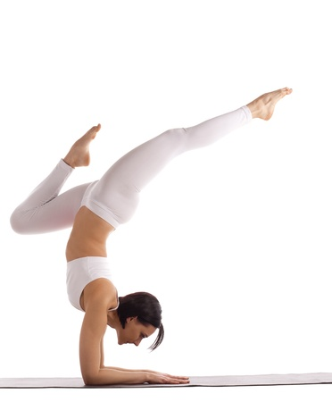 yoga studio: young woman in white stand on hands yoga asana isolated