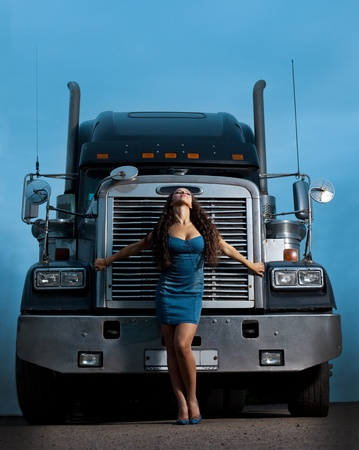 Young pretty girl posing before huge cargo truck at night Stock Photo