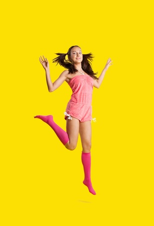 Beauty playful woman like girl jump on yellow photo