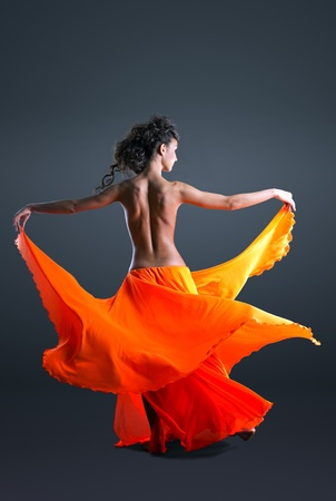 Beauty girl with spine dance in orange veil