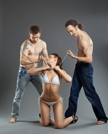 Two man take woman on chain in violence - bdsm games Stock Photo - 10412763