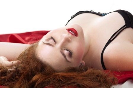 Beauty woman lay on red in lingerie  in desire close eyes Stock Photo - 10412764