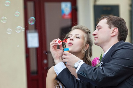 romance couple: just married young couple blow bubbles in town
