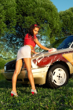 Sexy woman washing a car at summer sunset - pin-up style Stock Photo - 10509640