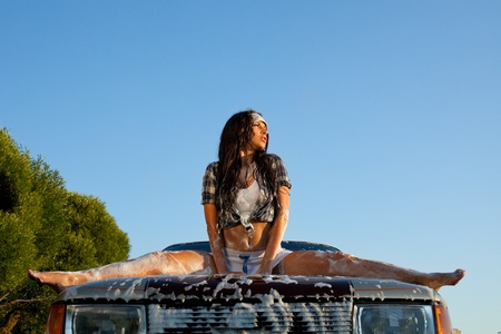 erotic dress: sexy young girl washing a car at summer sunset Stock Photo