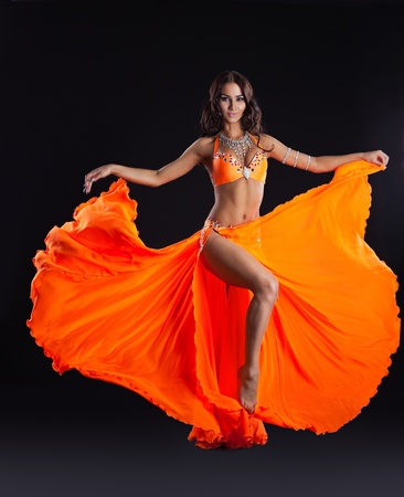 beauty young woman dance in orange veil arabic style costume Stock Photo