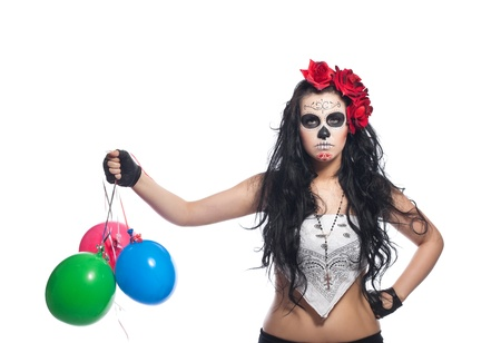 dia de los muertos: disappointed woman in day of the dead mask with ballons dressed up for All Souls Day