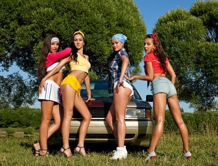 Four sexy pin-up woman near car with graffiti at summer sunset Stock Photo - 10593056